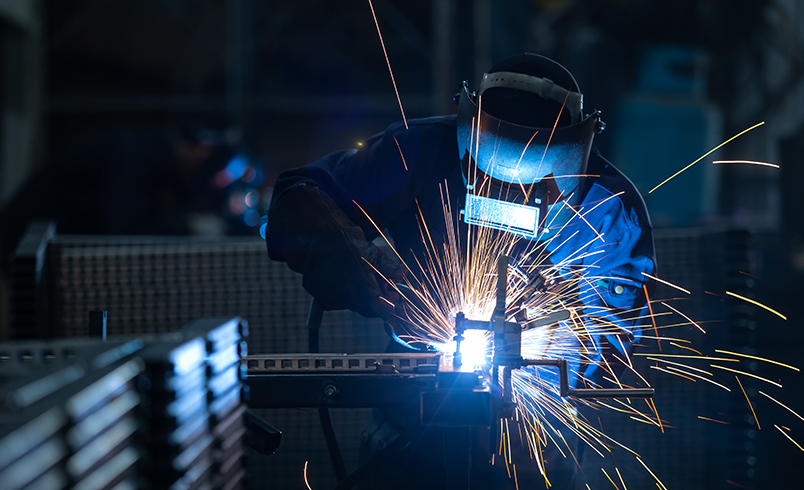 A person in full PPE welding in a workshop