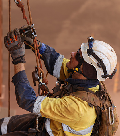 Image of a man in PPE and a safety harness performing work at height