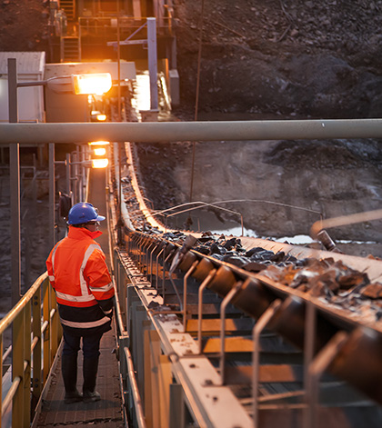 An image of a miner inspecting ore rocks on a conveyor at a mine site in New South Wales Australia
