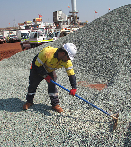 an image of a Unite Resourcing employee raking blue metal in PPE - high visibility clothing and hardhat