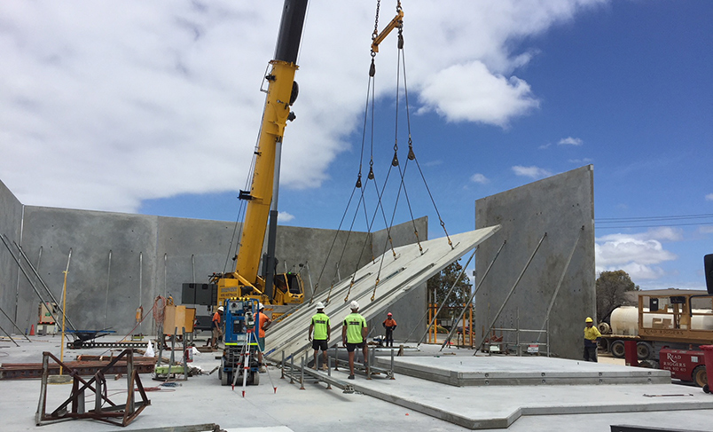 Construction workers lifting concrete slabs using a crane