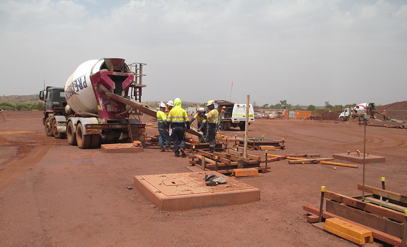 A group of workers in PPE tipping concrete from a cement truck
