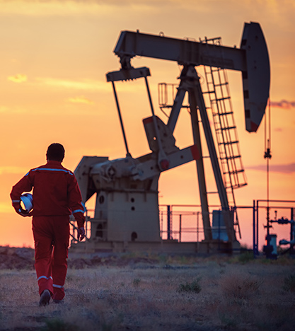 a man wearing high visibility ppe walking toward an oil rig at sunset